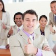 Successful manager in front of his team with thumbs up — Stock Photo