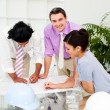 Stock Photo: Multi-ethnic architect co-workers reviewing blueprints