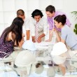 A team of architects at the meeting looking at blueprints — Stock Photo #10288380