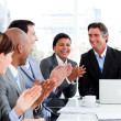 Smiling multi-ethnic business team applauding - Stock Photo