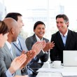 Foto Stock: Smiling multi-ethnic business team applauding
