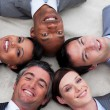 Multi-ethnic business team lying on the floor with heads togethe — Stock Photo