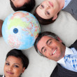 Multi-ethnic business team lying on the floor around a terrestri — Stock Photo #10289050