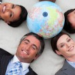Foto Stock: Business lying on floor around terrestrial globe