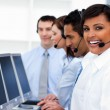 Happy co-workers with headsets on working in call center — Stock Photo #10289053