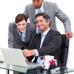 Joyful businessman showing something at laptop to his team — Stock Photo