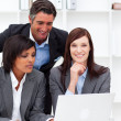 Stock Photo: Positive businesswomen and their colleague working at a laptop