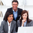 Stock Photo: Serious businesswomen and their colleague working at a laptop