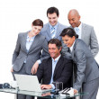 Cheerful international business team looking at a laptop — Stock Photo