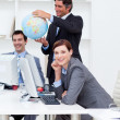 Royalty-Free Stock Photo: Happy manager holding a globe with his team working at computers