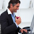 Happy businessman eating a red apple — Stock Photo