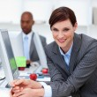 Royalty-Free Stock Photo: Smiling businesswoman at work with her colleague in the backgrou