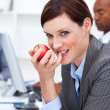 Businesswoman eating a fruit at work — Stock Photo