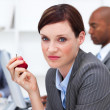 Stock Photo: Young businesswoman eating an apple