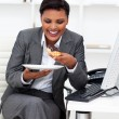 Happy businesswoman eating in the office — Stock Photo