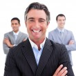 Stock Photo: Enthusiastic businessmposing in front of his team