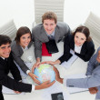 Foto Stock: Smiling Business team holding terrestrial globe