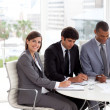 Stock Photo: Young businesswoman sitting at a conference table with her team