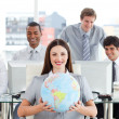 Brunette businesswoman and her team showing a terrestrial globe — Stock Photo