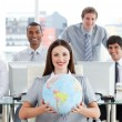 Pretty businesswoman and her team showing a terrestrial globe - Stock Photo