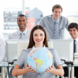 Pretty businesswomand her team showing terrestrial globe — Stock Photo #10289914
