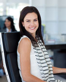 Smiling businesswoman sitting in her workplace — Stock Photo