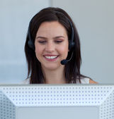 Beautiful businesswoman in a call centre with a headset on — Stock Photo