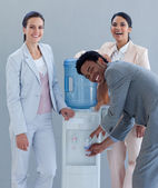 Business team drinking from a water cooler — Stock Photo
