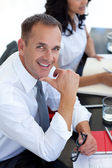 Businessman in a meeting smiling at the camera — Stock Photo