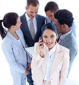 Businesswoman on phone and her team in the background — Stock Photo