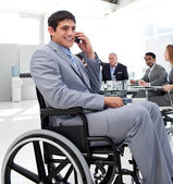 Businessman in a wheelchair on phone during a meeting — Stock Photo
