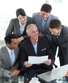 Happy multi-ethnic business group studying a document — Stockfoto