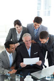 Businessman showing a contract to his team — Stock Photo