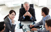 Multi-ethnic business sitting around a conference table — Stock Photo