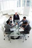 握手围坐在会议桌的商人 — 图库照片