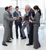 Cheerful manager serving Champagne to his team — Stock Photo
