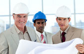 Smiling architects studying blueprints — Stock Photo