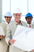 Attractive architect holding blueprints — Stock Photo