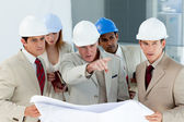 Serious architect looking at blueprints and pointing — Stock Photo