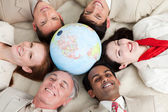A diverse business lying on the floor around a globe — Stock Photo