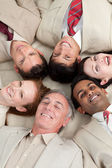 Multi-ethnic business team lying in a circle — Stock Photo