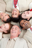 Laughing Business team lying in a circle — Stock Photo