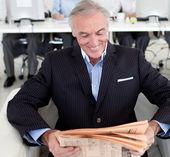 Senior businessman reading a newspaper — Stock Photo