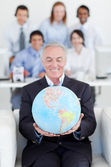 Senior businessman holding a terrestrial globe — Stock Photo
