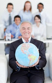 Senior manager holding a terrestrial globe — Stock Photo
