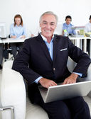 Smiling businessman using a laptop — Stock Photo