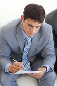 Concentrated businessman writing while waiting for a job intervi — Stock Photo