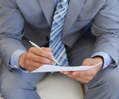 Close-up of a businessman writing on a paper — Stock Photo