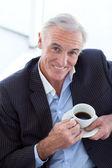 Empresario bebiendo y sentado en una sala de espera — Foto de Stock