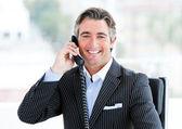 Self-assured mature businessman talking on phone — Stock Photo
